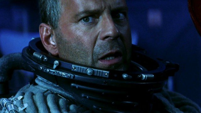 A close-up of Bruce WIllis, wearing a helmetless astronaut suit in 'Armageddon'.