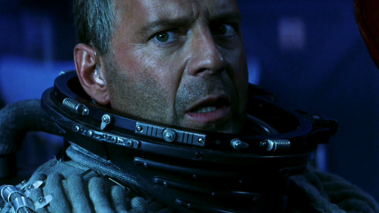 A close-up of Bruce WIllis, wearing a helmetless astronaut suit in Armageddon