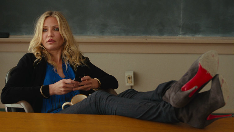 Cameron Diaz with her feet up on a desk, looking straight ahead