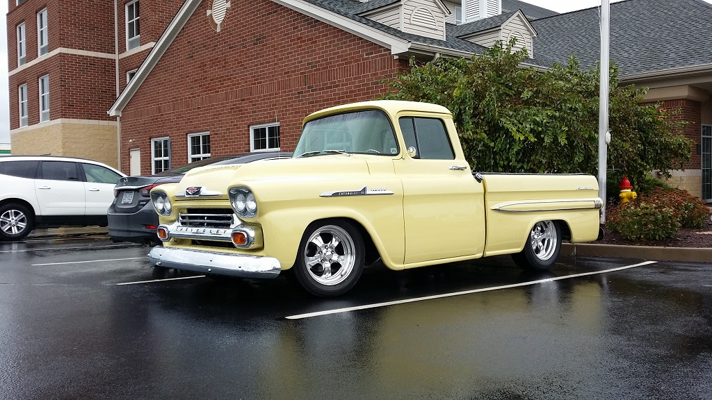 A canary yellow Chevy Apache Fleetside sits parked in a designated parking spot