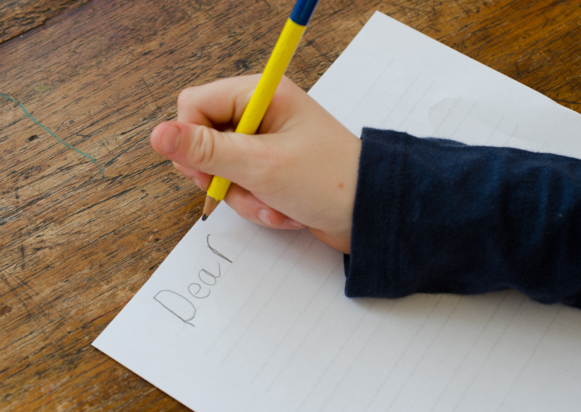 small child begins to write a letter