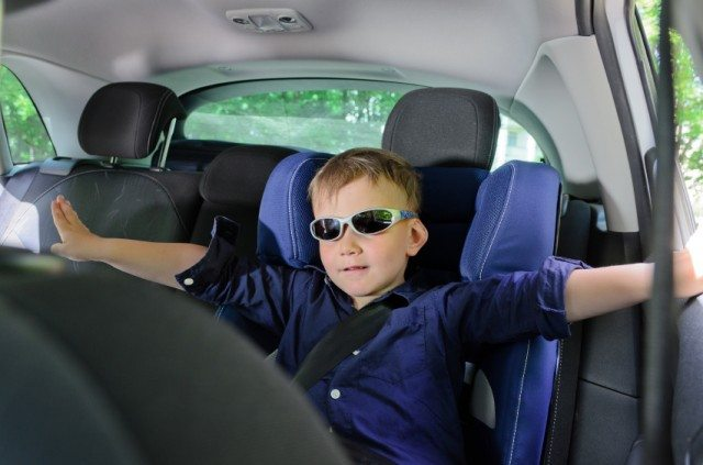 boy wearing sunglasses and sitting in a booster seat