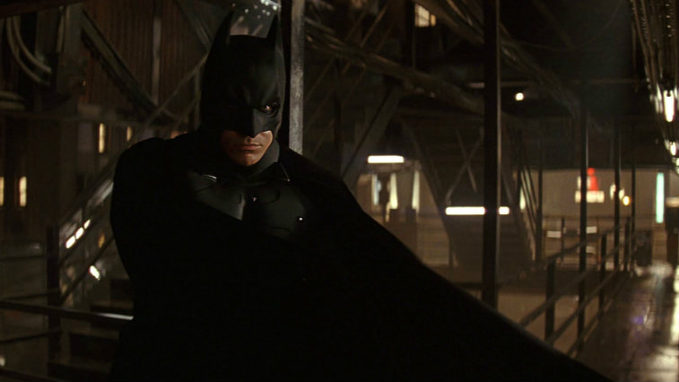 Christian Bale in Batman Begins, scowling at the camera and crouched down