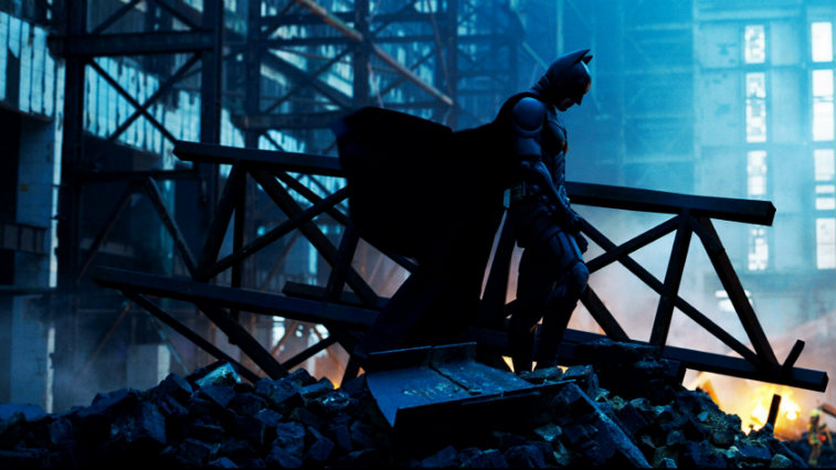 The silhouette of Christian Bale's Batman standing in wreckage in The Dark Knight