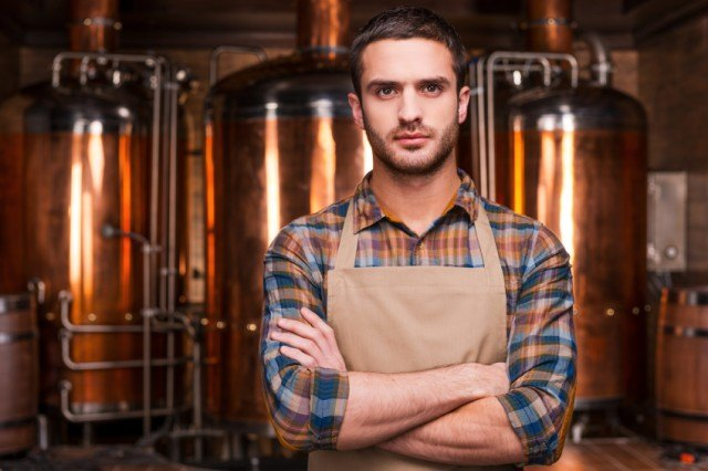 Young brewer in front of metal containers