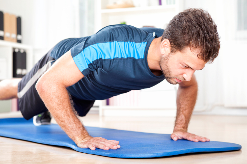 Man doing plank position on a mat at home