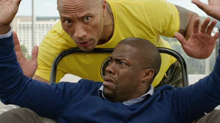 Kevin Hart looking distressed with his hands up, with the Rock behind him in a yellow shirt