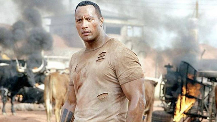 A sweat-caked Dwayne Johnson wearing a torn tshirt, looking to the left of the frame