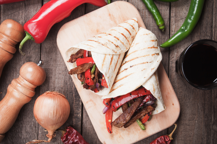 Fajitas on wooden board with vegetables