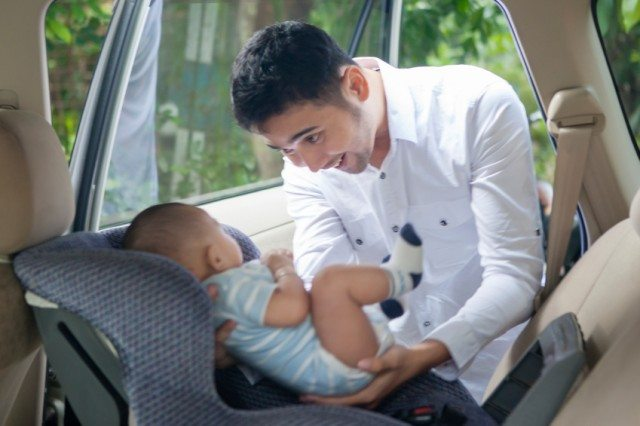 Father Putting his Baby in a Car Seat