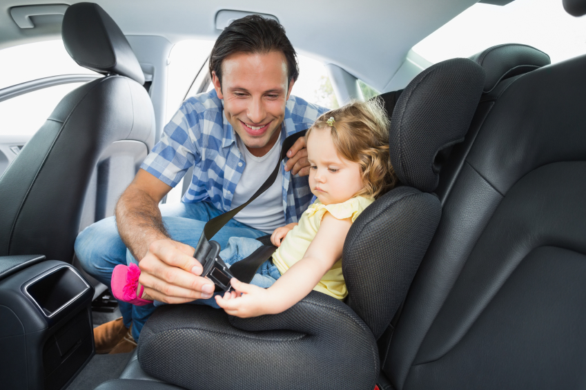 father fastening seatbelt of a baby in car