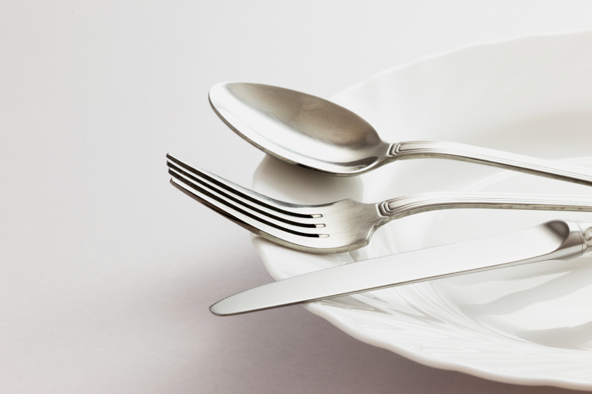 a silver fork, spoon and knife on a white plate