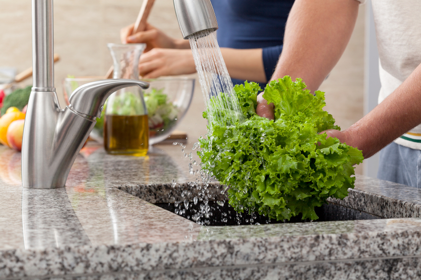 people washing lettuce for salad