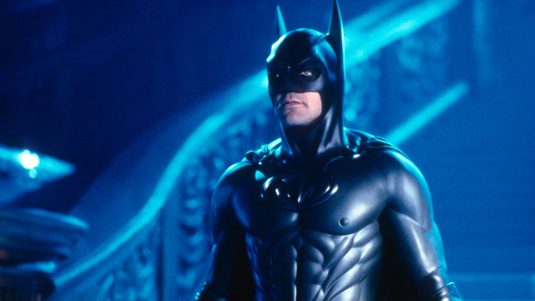 George Clooney wears a Batman suit and stands at the bottom of stairs in Batman and Robin