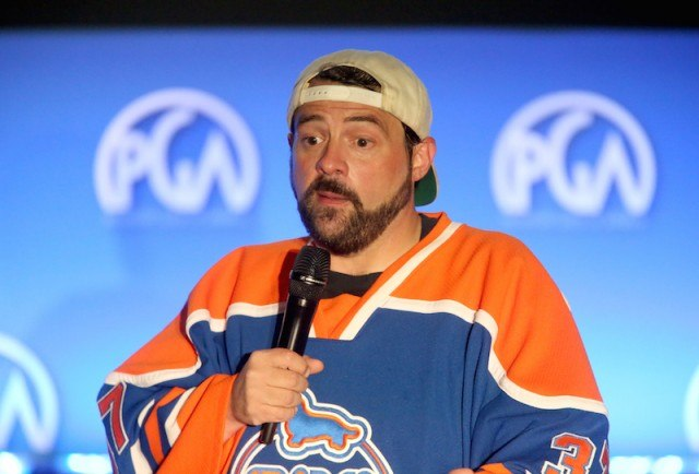 Kevin Smith speaks at a press panel wearing a blue and orange jersey.