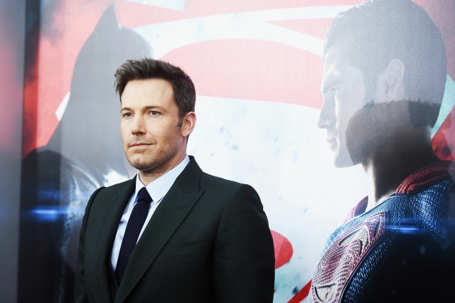 Ben Affleck is smiling in front of a 'Batman V Superman: Dawn Of Justice' poster.