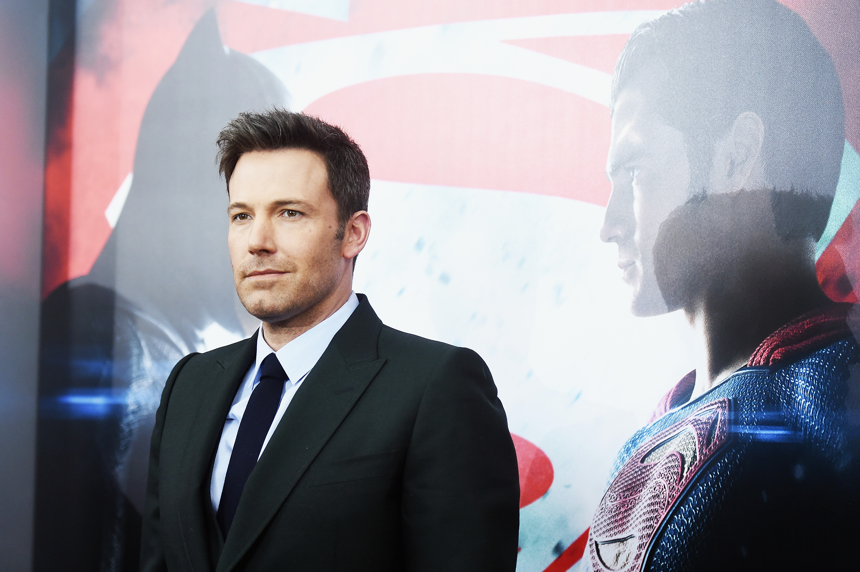 Ben Affleck is smiling in front of a Batman V Superman: Dawn Of Justice poster.