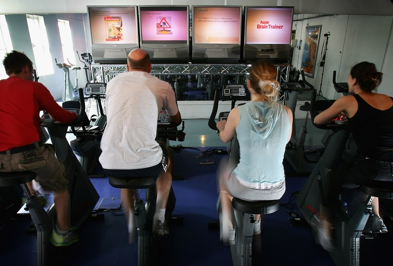 Men and women exercise on stationary bikes