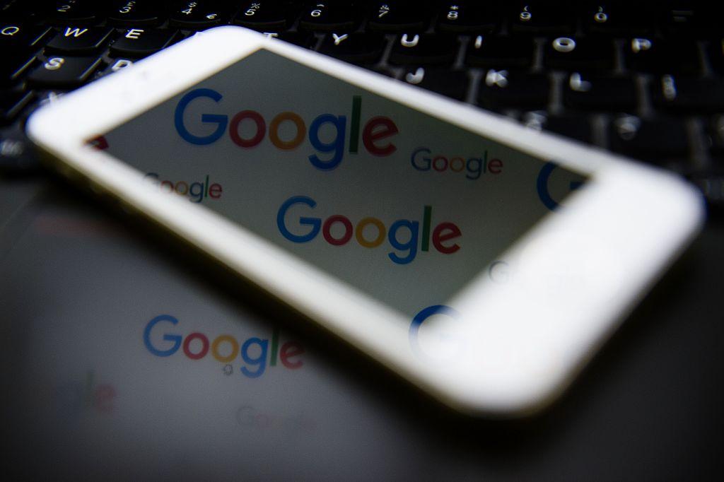 Smartphone refelecting Google logos on a laptop