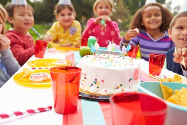 kids celebrate at an outdoor birthday party, getting ready to eat cake