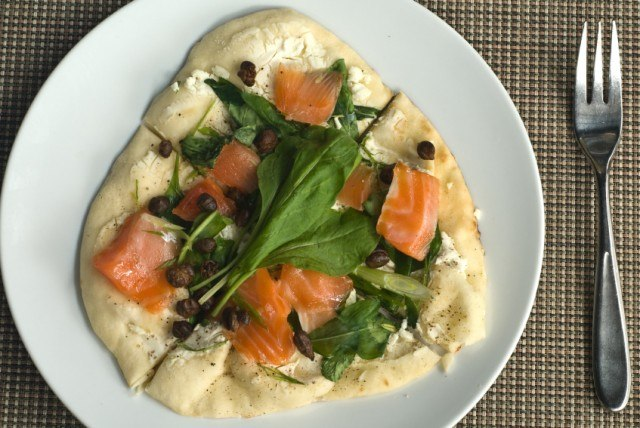 overhead image of a salmon pizza with herbs, and capers