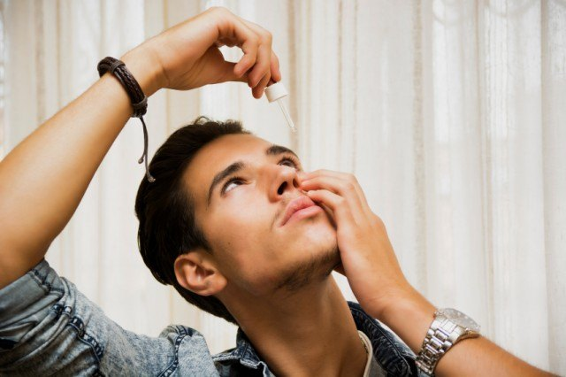 young man dropping medicine in his eye