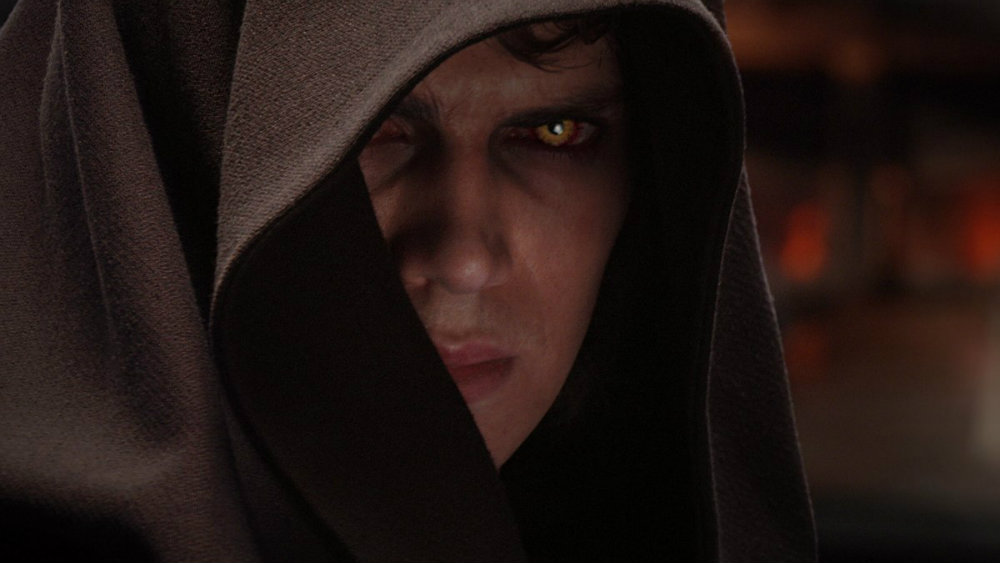 Anakin wearing a brown hood, with sinister yellow eyes, angrily staring into the camera