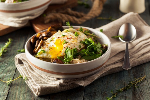 bowl of savory oatmeal topped with eggs, herbs, and mushrooms