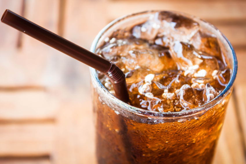 glass of cola with ice cubes and a straw