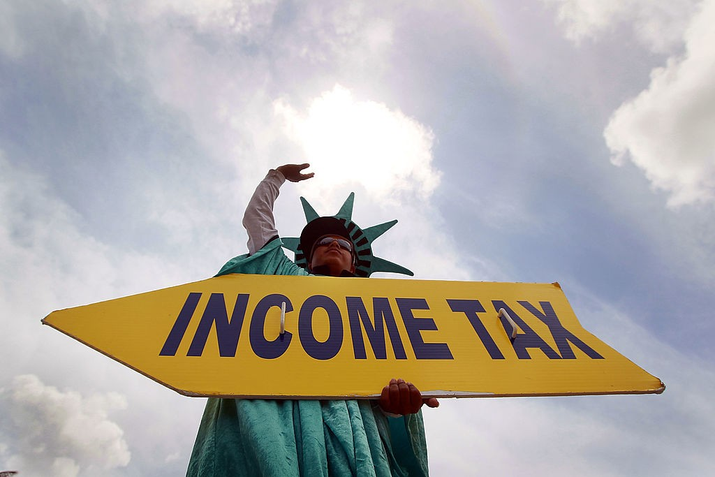 man holds income tax sign