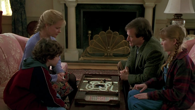 The cast of Jumanji gathers around the game board in a living room preparing to roll the dice