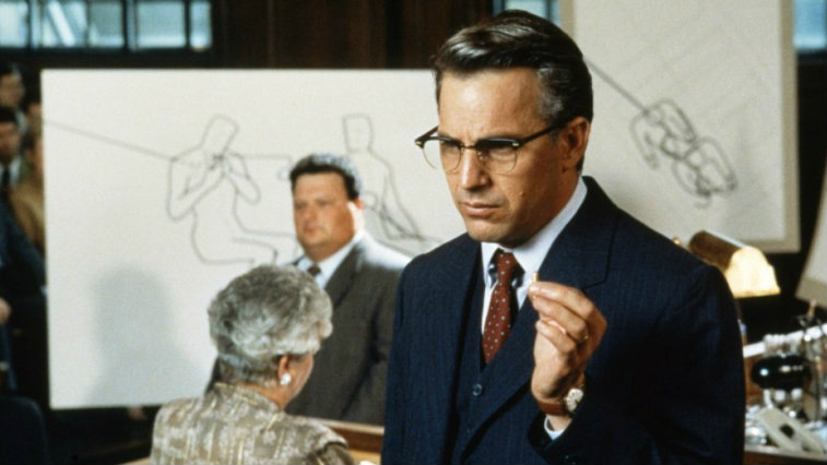 Kevin Costner is in a blue suit and wearing glasses in JFK.