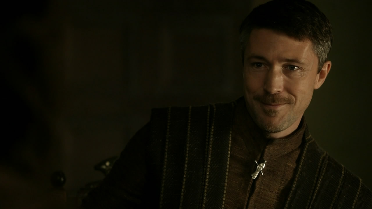 Littlefinger is smiling and leaning against something.