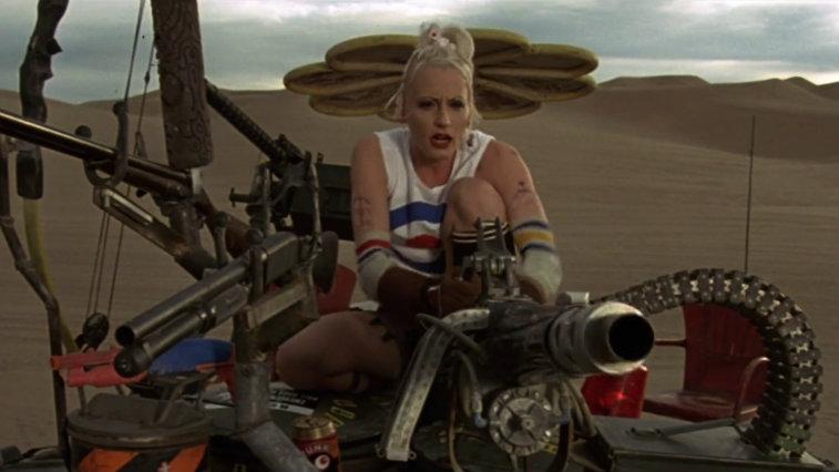 Lori Petty in the desert riding a large machine in Tank Girl