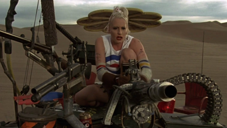 Lori Petty in the desert riding a large machine in Tank Girl