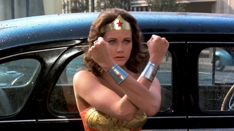 Lynda Carter as Wonder Woman holding her arms in an X-formation in front of a car