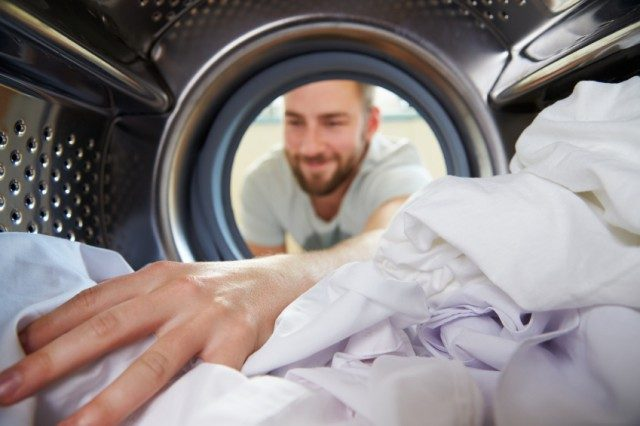 A man doing laundry reaches for his clothes.