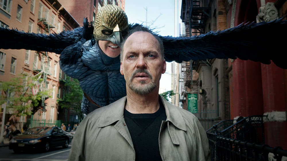 Michael Keaton walking on a city street, as his own character Birdman flies behind him