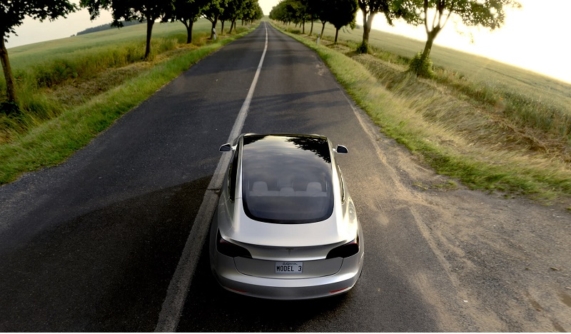 A silver Tesla Model 3 driving down a scenic road