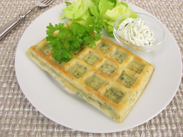 herb waffles on a plate with lettuce, parsley, and cream cheese
