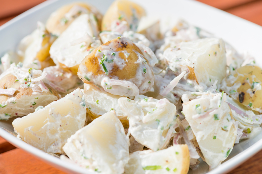 close-up of creamy potato salad with herbs and shallots