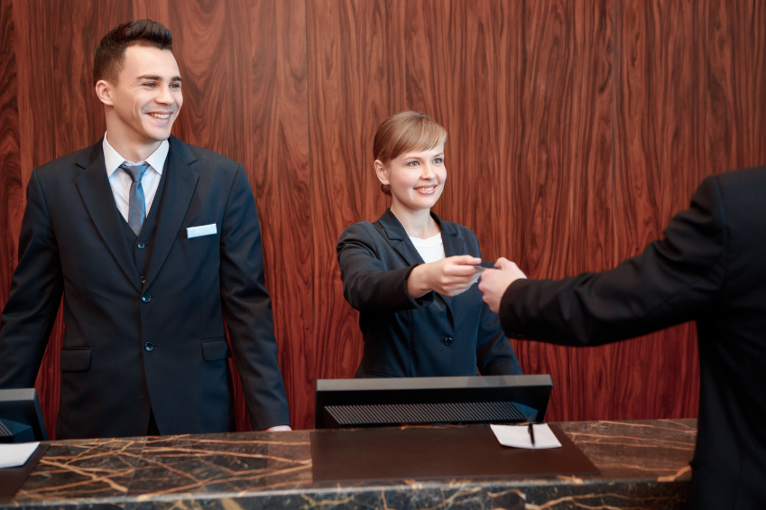 female and a male receptionist welcoming guest and giving the room key