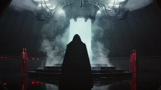 A dark hooded figure walking in front of a bright laser and smoke.