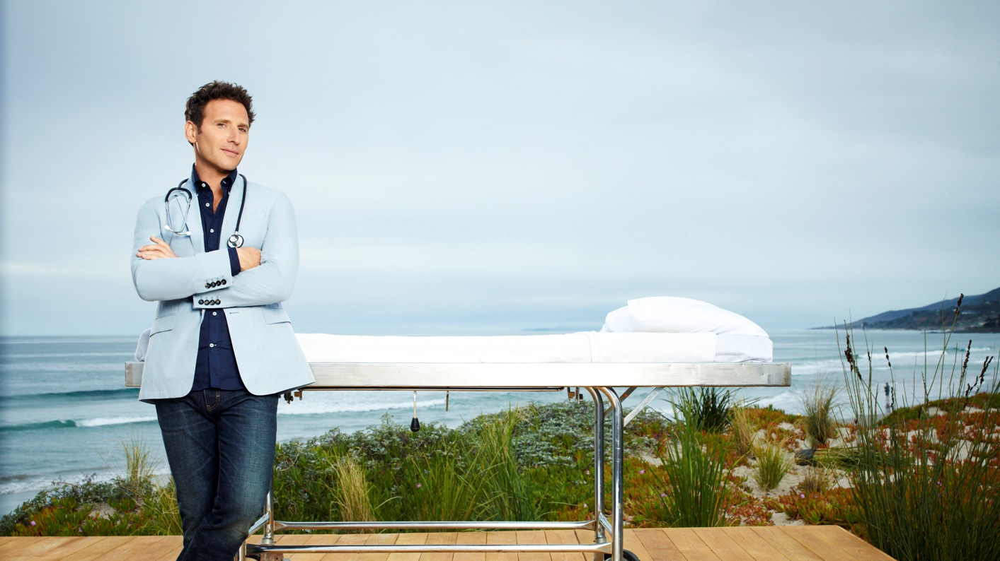 Mark Feuerstein stands on a beachside deck in a promotional poster for Royal Pains