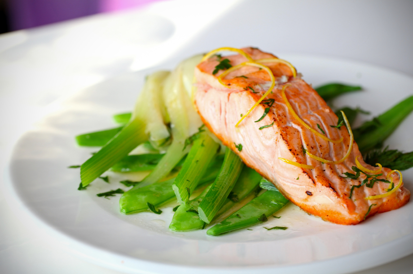 seared salmon with lemon zest and fennel on a white plate