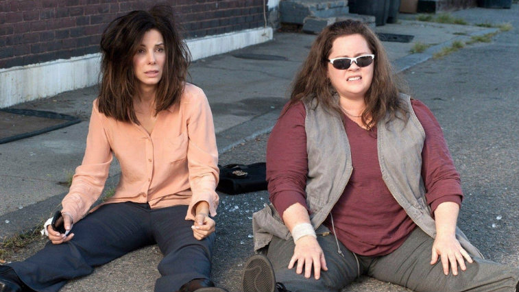 Sandra Bullock and Melissa McCarthy are sitting down on the ground in The Heat.