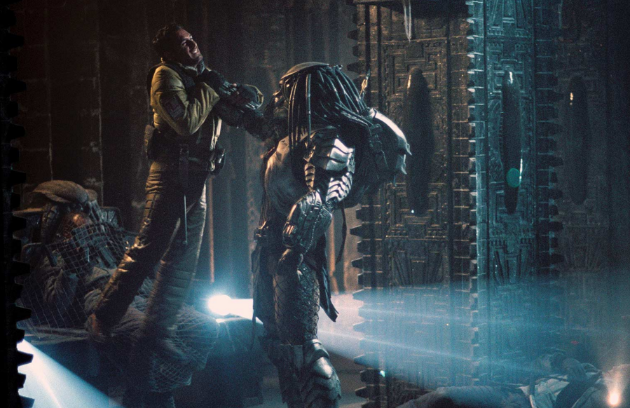 The Predator lifts and chokes a man inside of an ancient temple