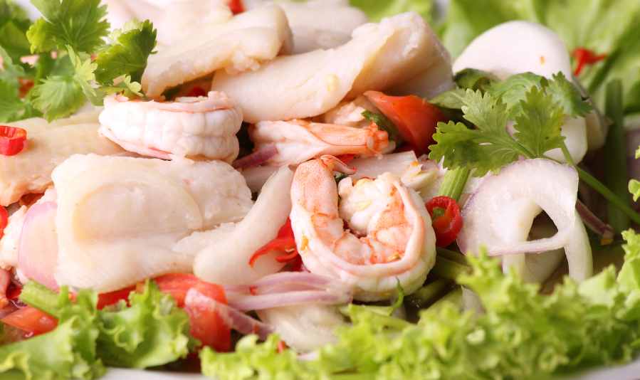 close-up of a Thai seafood salad with lettuce and fresh herbs