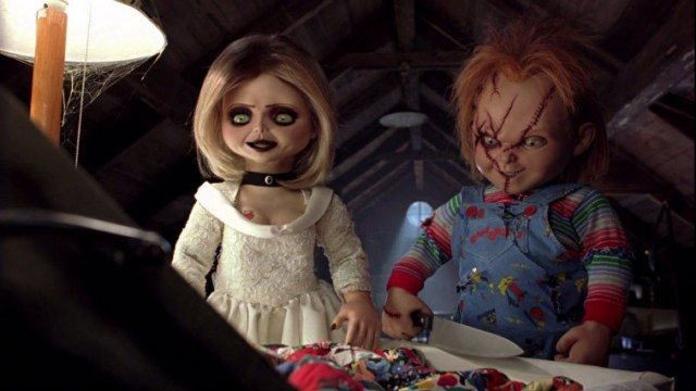 Jennifer Tilly and Chucky sitting at a table.