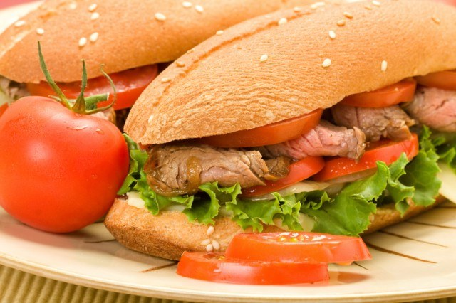 close-up of a juicy steak sandwich with tomatoes and lettuce